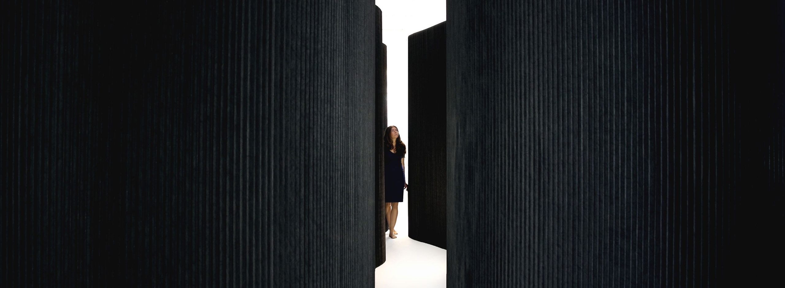 woman wanders through black textile softwall