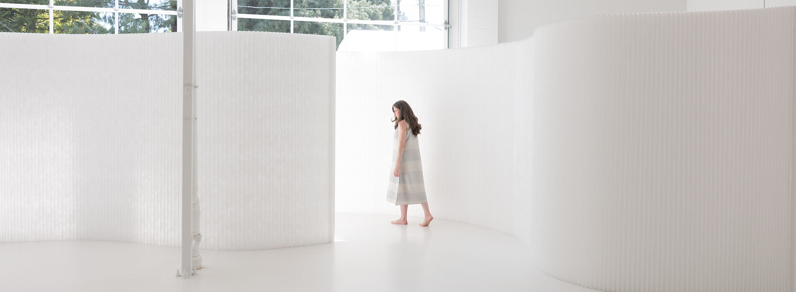 A translucent interior partition, textile softwall is a flexible folding wall that can be adjusted to any shape to create a sculptural backdrop or divide space.