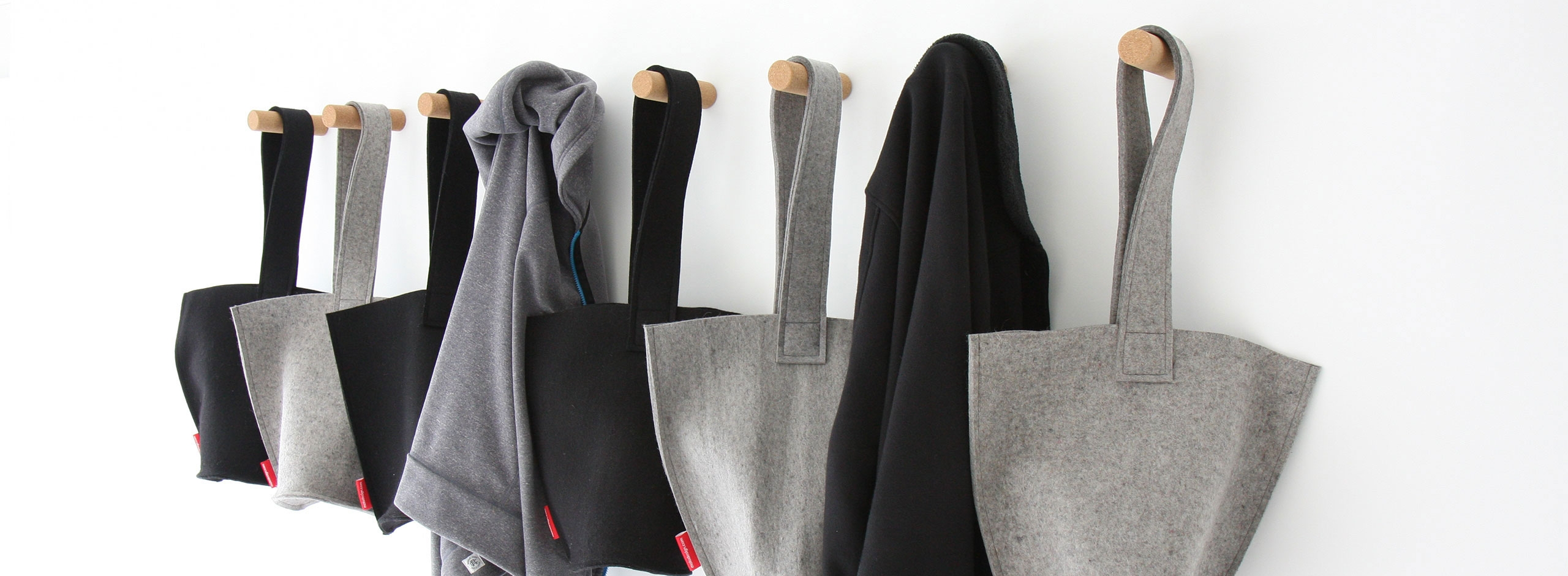 sweaters and hobo bag hangs from cork peg