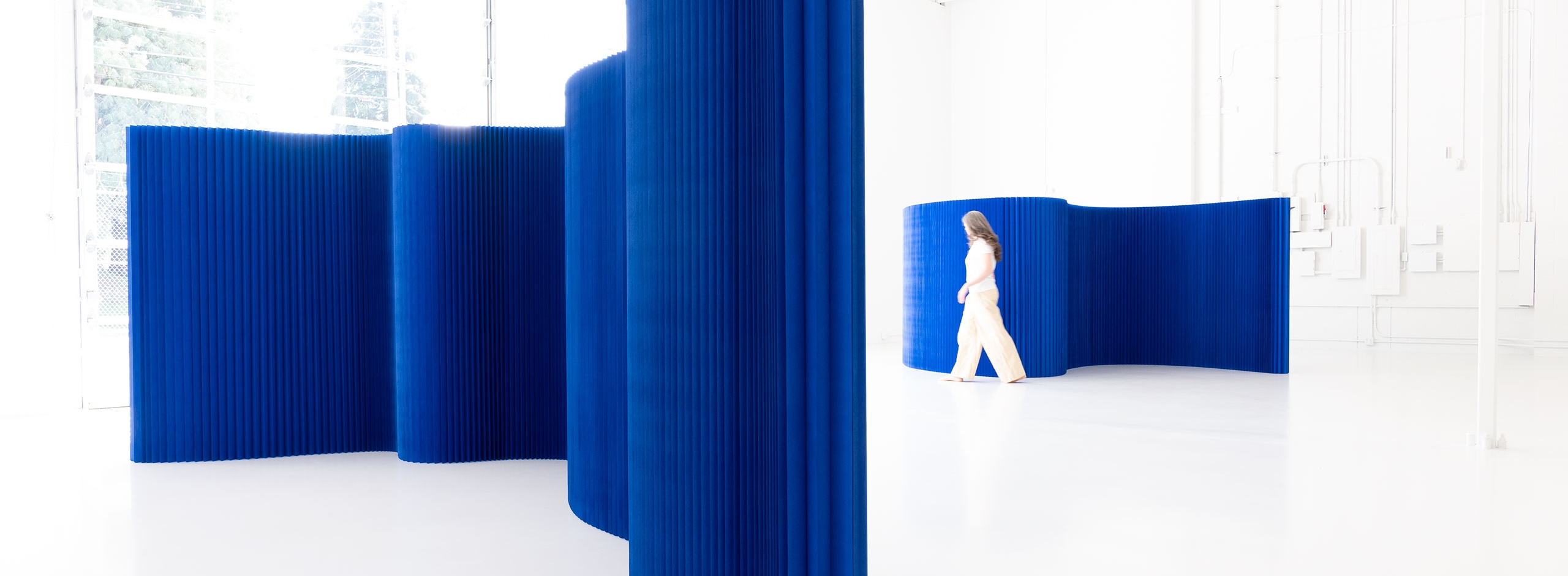 The paper wall by molo is a freestanding flexible space partition. This blue version of the softwall room divider both absorbs and radiates light.