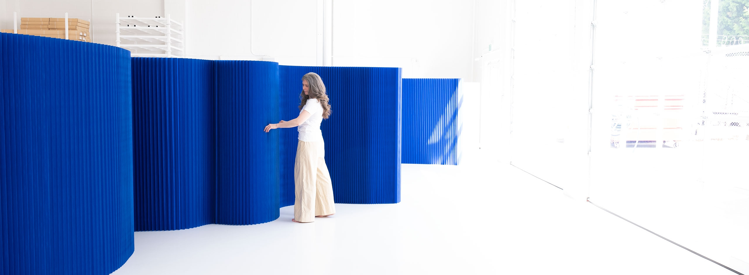 This blue wall is a a flexible room divider made from paper. As a dramatic backdrop for special events or daily life these movable partitions can be made into any shape and easily flat pack for storage and portability.