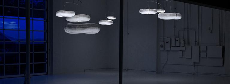 cloud softlight mobile inhabit a dark, open space.