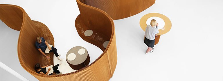 Benchwall expanding paper bench that is also a an acoustic space partition. The flexible shape can change from a meeting room to more open seating area