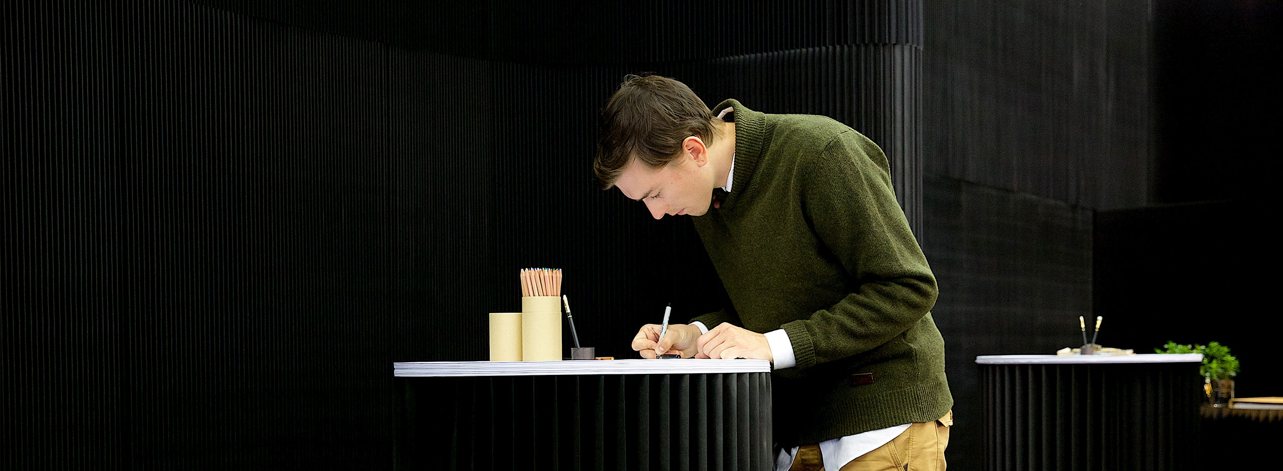 man draws on a sketching circle in front of a black thinwall