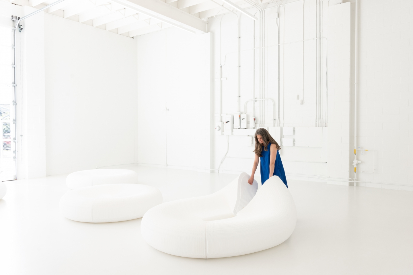 a woman magnetically connects the flexible, foldable honeycomb segments of molo softseating lounger