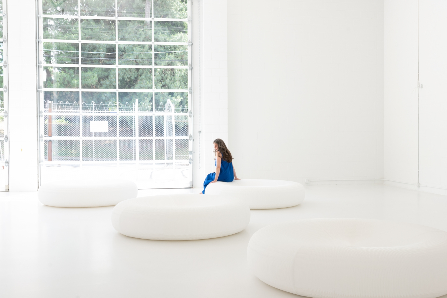 a woman perches on molo's white textile lounger, a Tyvek honeycomb seat