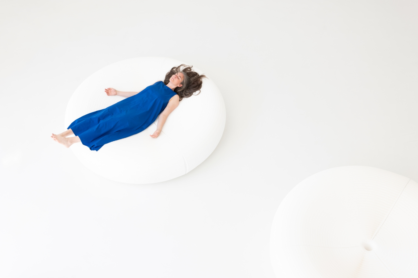 a woman reposes on molo white textile lounger, a large honeycomb pouf