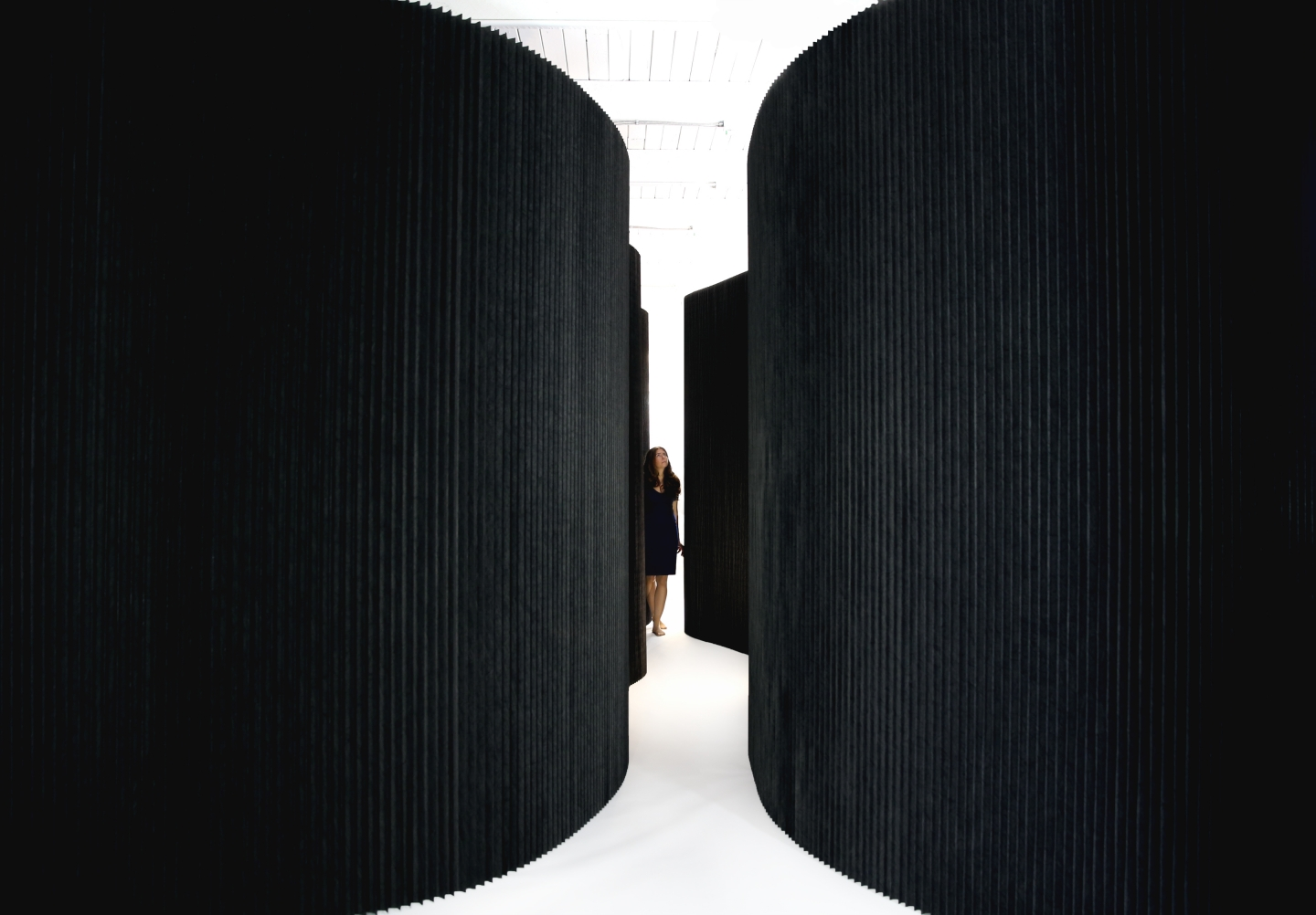 woman drifts through an installation of black softwalls -
