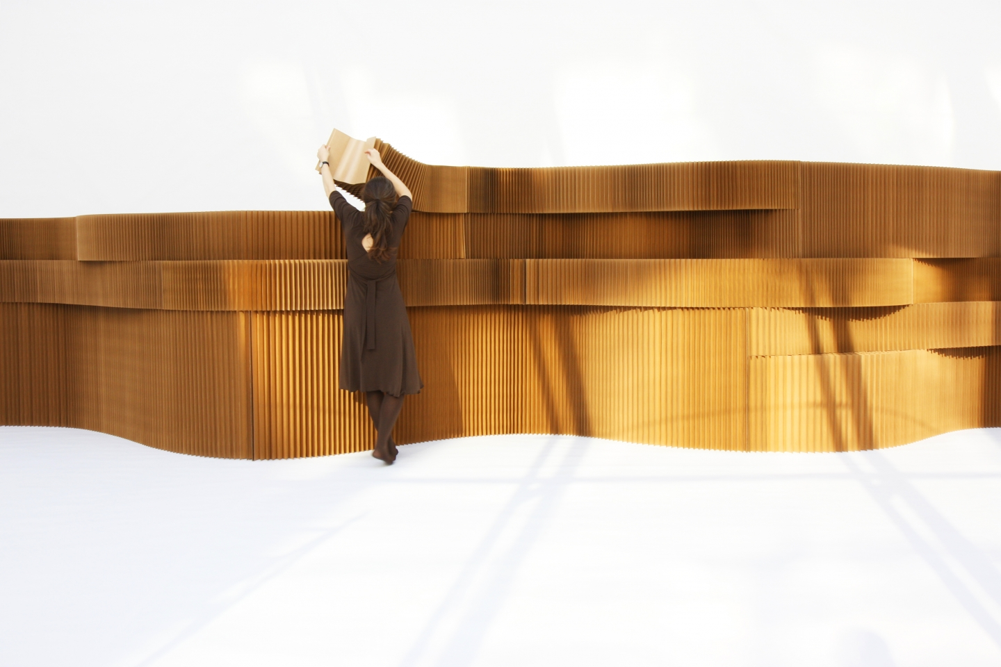 woman arranges stacked brown paper softblocks - moveable modular wall divider system
