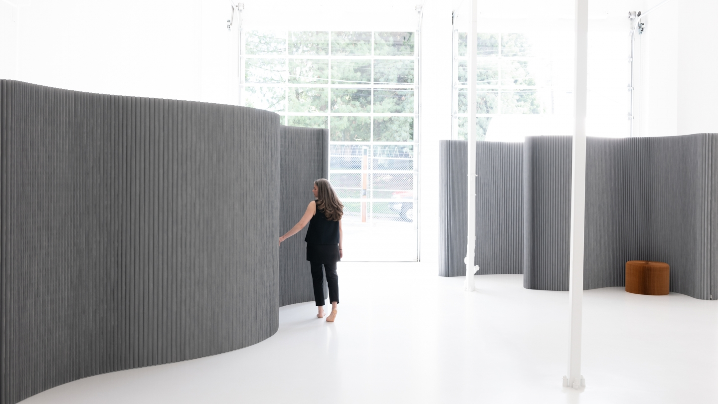 Stephanie Forsythe runs a hand along the pleats of a paper room divider.
