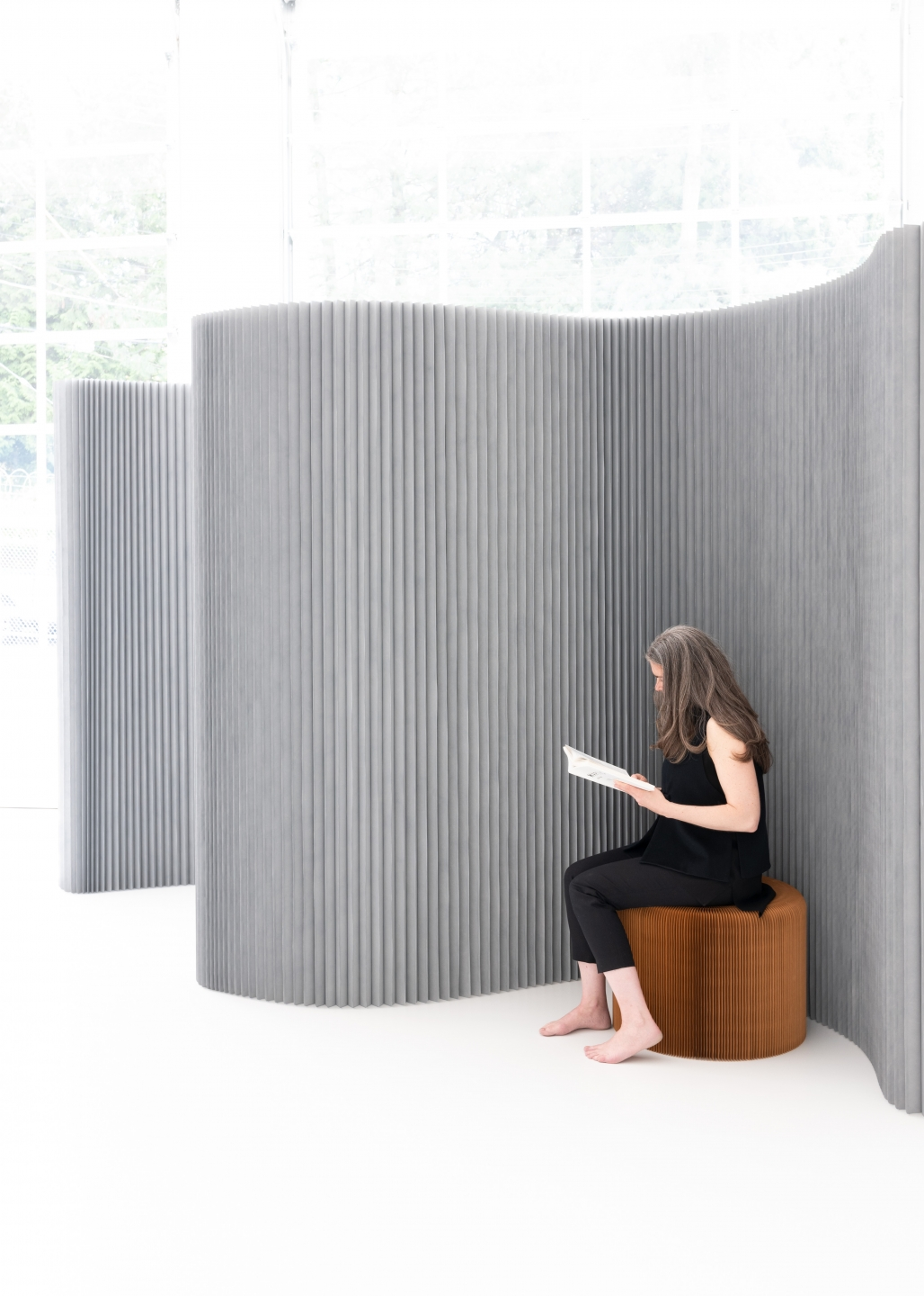 A textile softwall arranged to form a private reading nook.