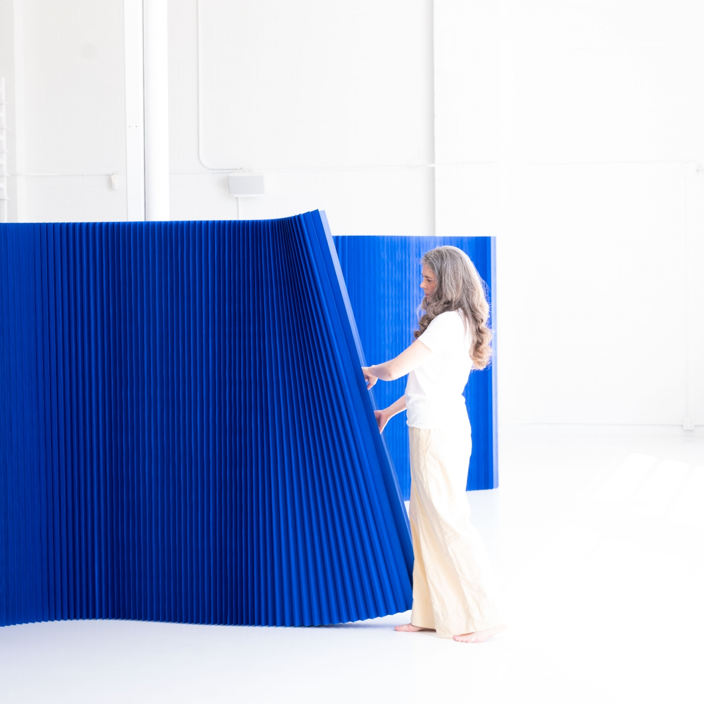 Demonstrating how softwall moves - moveable office wall divider by molo - indigo colour