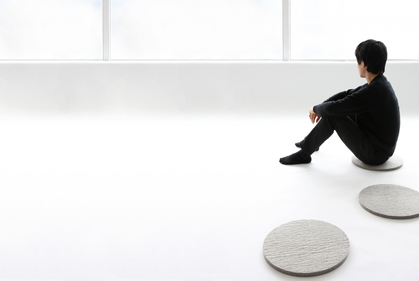 a man uses wool felt pads as simple floor cushions
