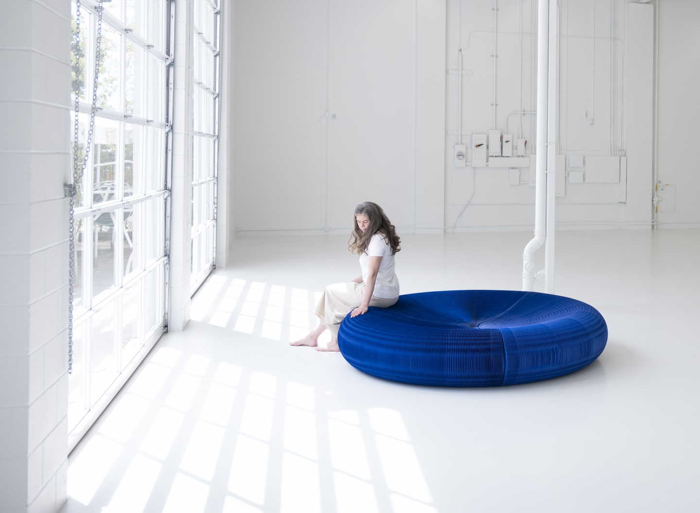 A woman sits on a blue paper softseating lounger.