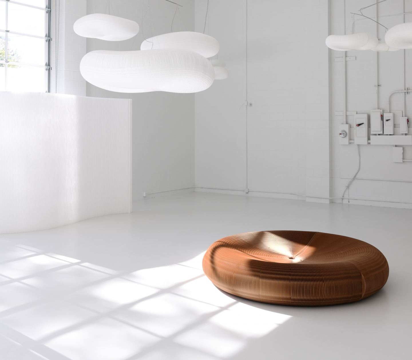 A paper softseating lounger rests on the floor below a series of cloud softlight mobiles.