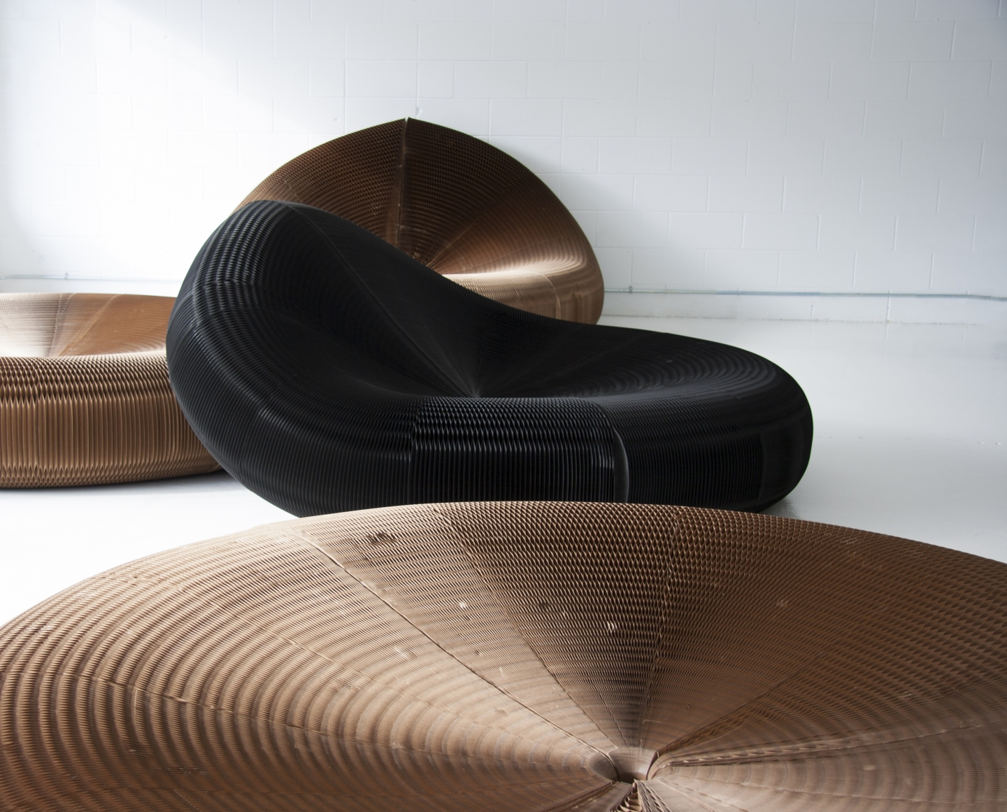 a black paper softseating lounger leans against another to create a contoured backrest.