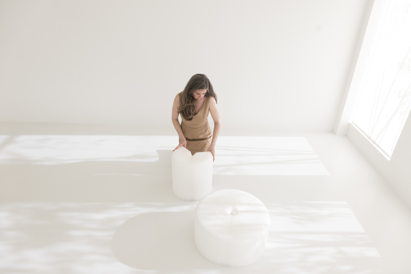 A woman closes a textile softseating fanning stool by its magnetic end panels.