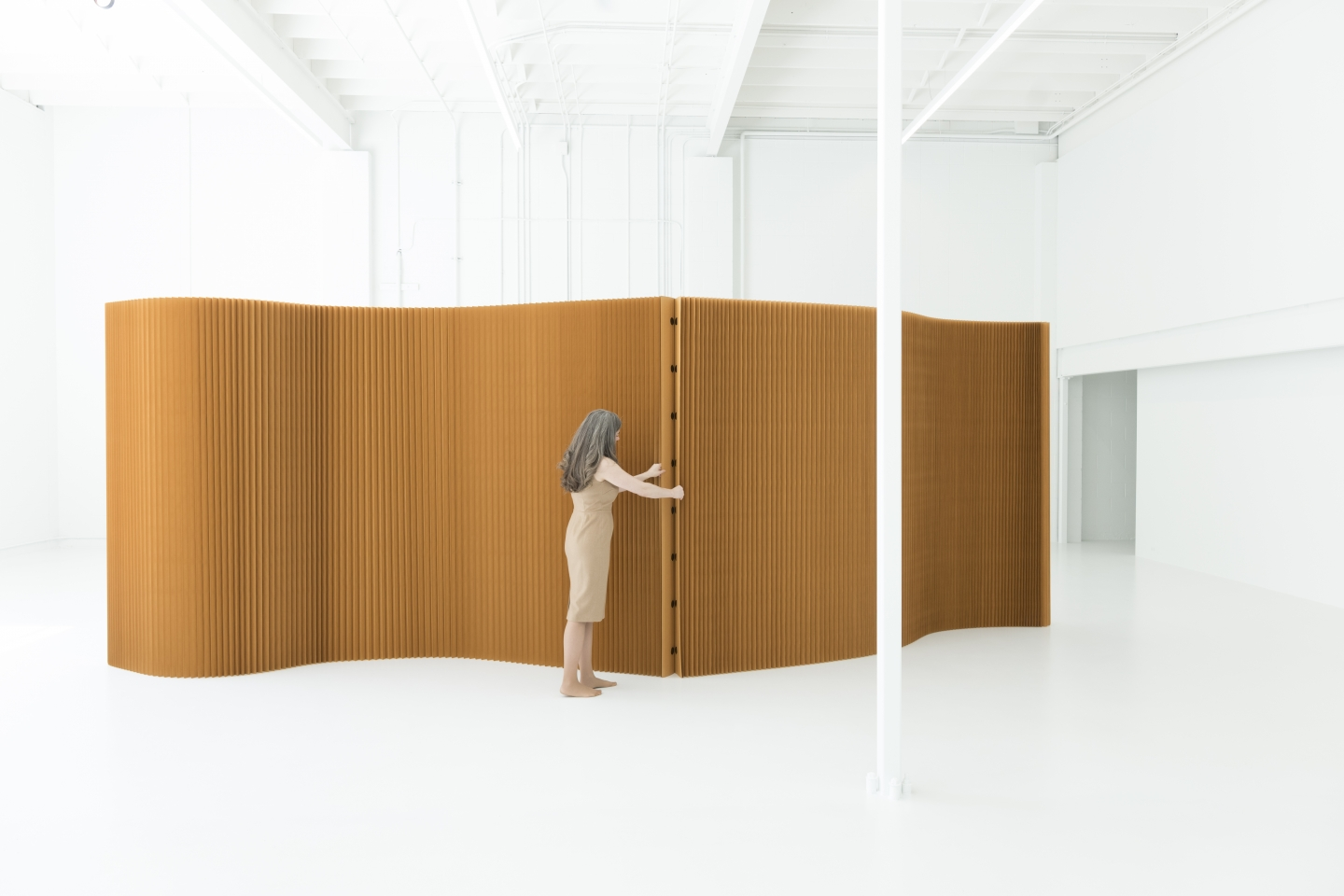 A woman connects two paper softwalls by their magnetic end panels.