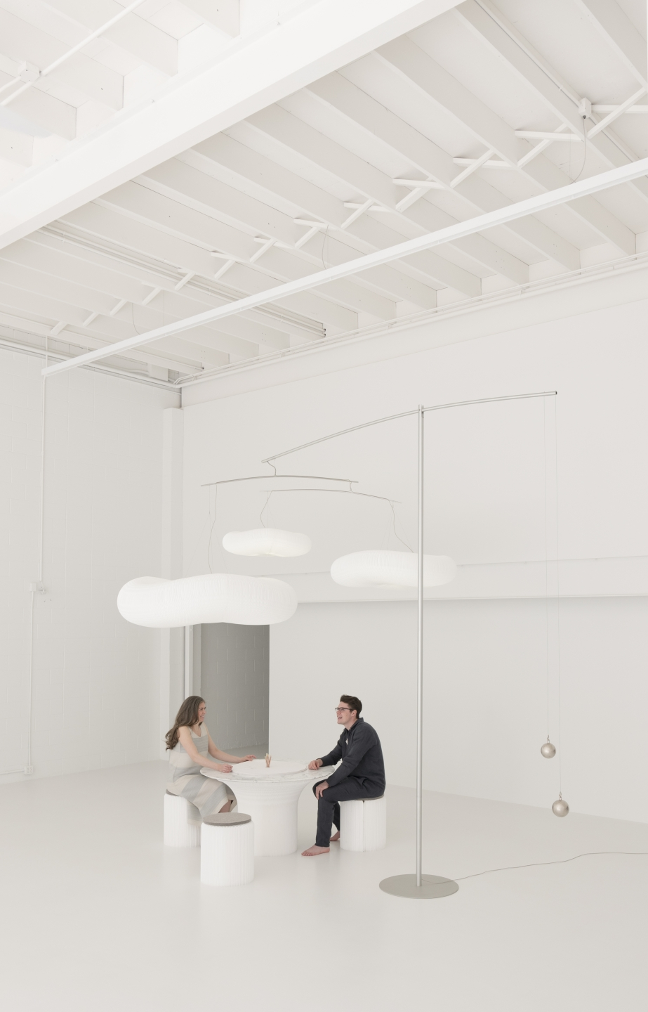 two people chat while sitting at a cantilever table underneath cloud mast