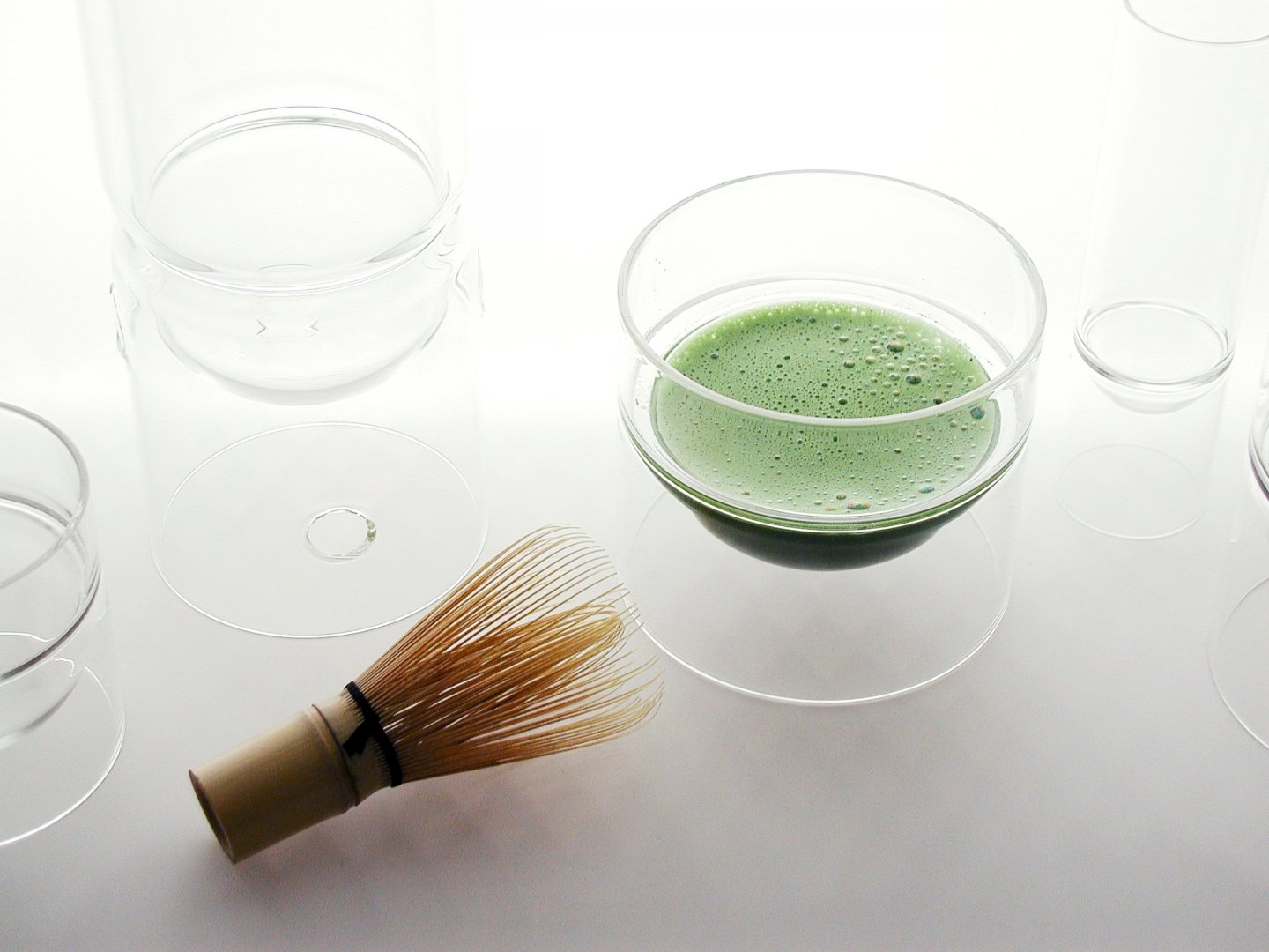 a bowl full of matcha and a traditional bamboo whisk