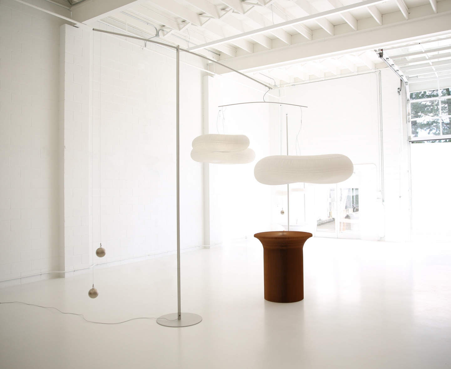 cloud mast holds two fishing weights and a cloud mobile in delicate balance