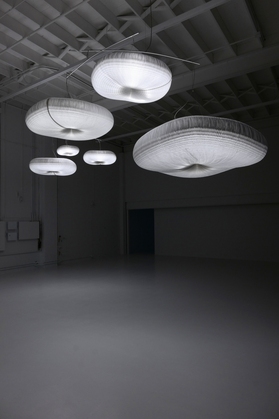 a mysterious canopy of cloud mobiles hang illuminated in the dark