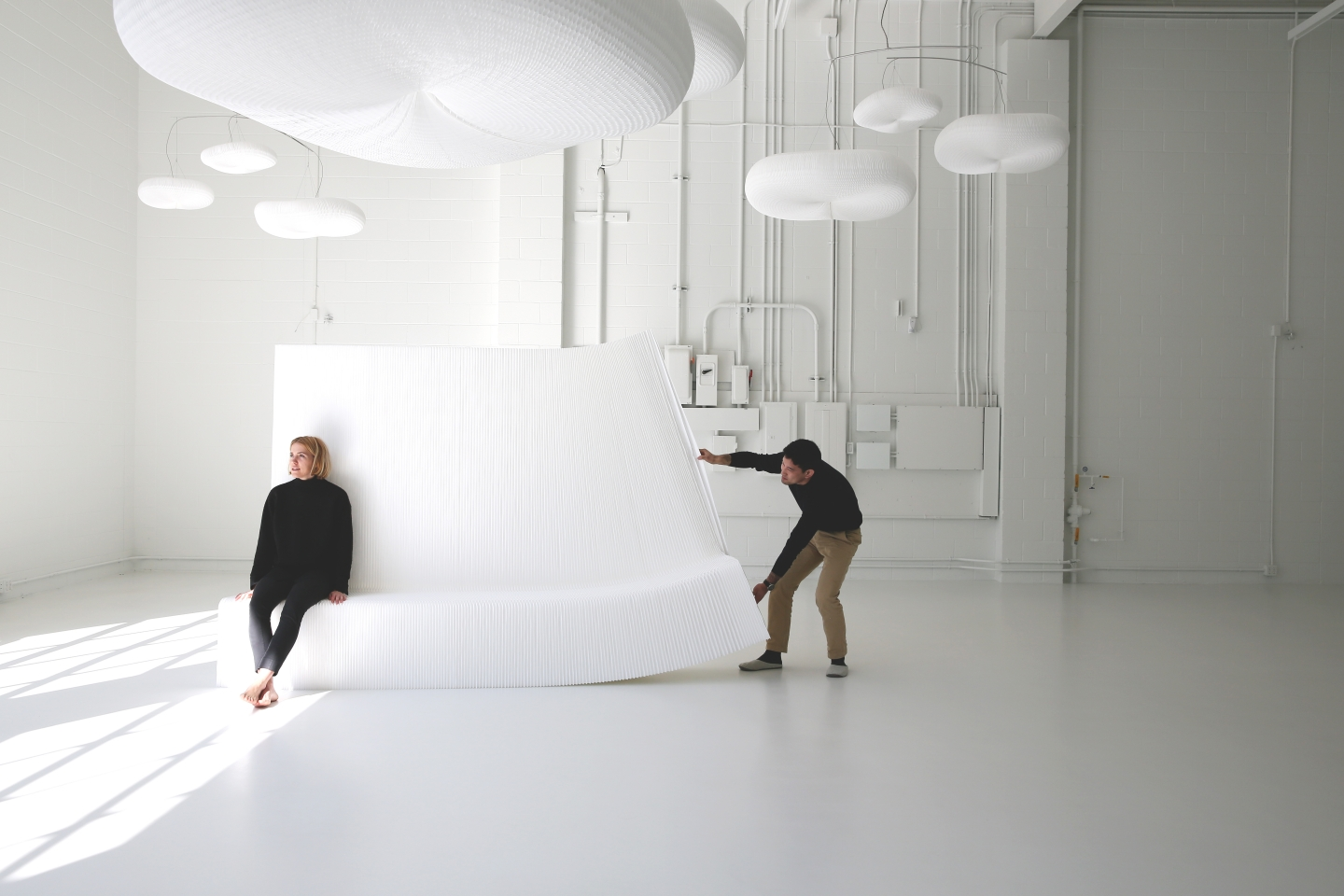 stretching open a white textile benchwall underneath a canopy of cloud mobiles