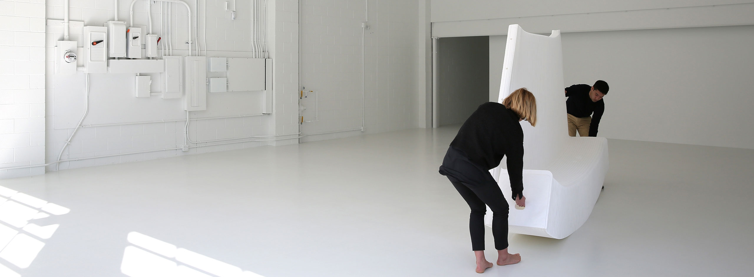 two people stretch open a white textile softwall