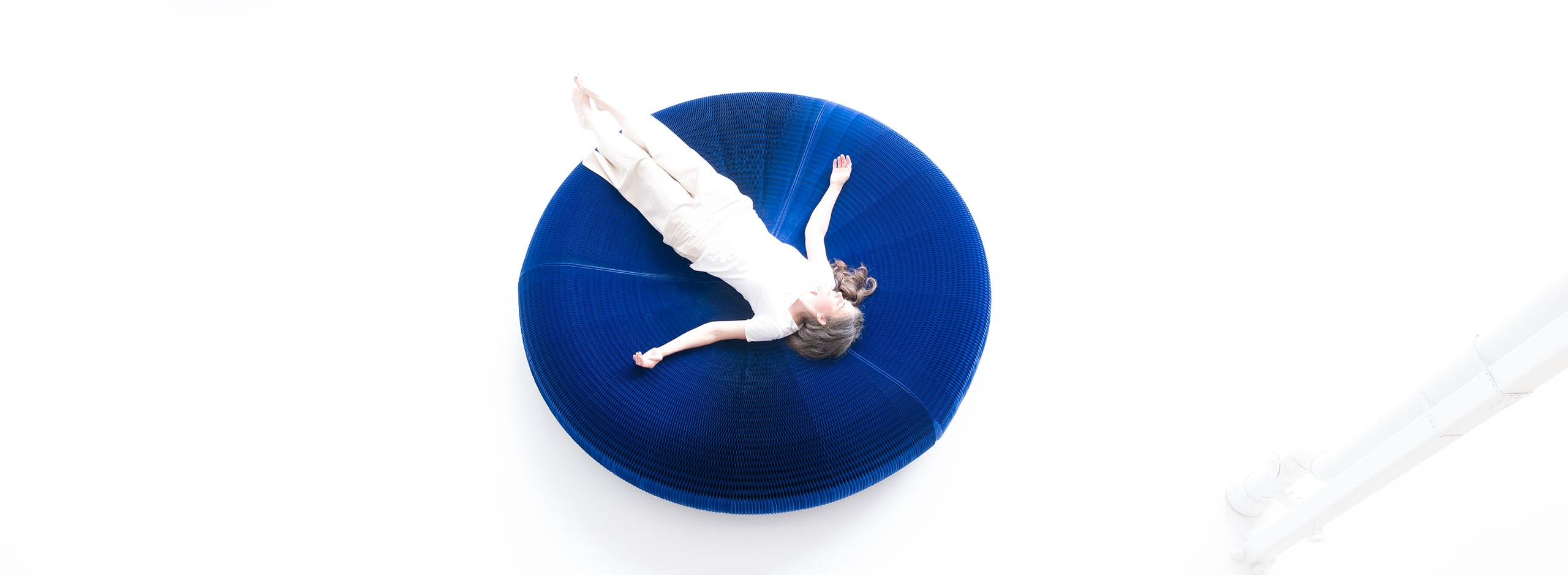 overhead view of a woman laying on an indigo paper lounger