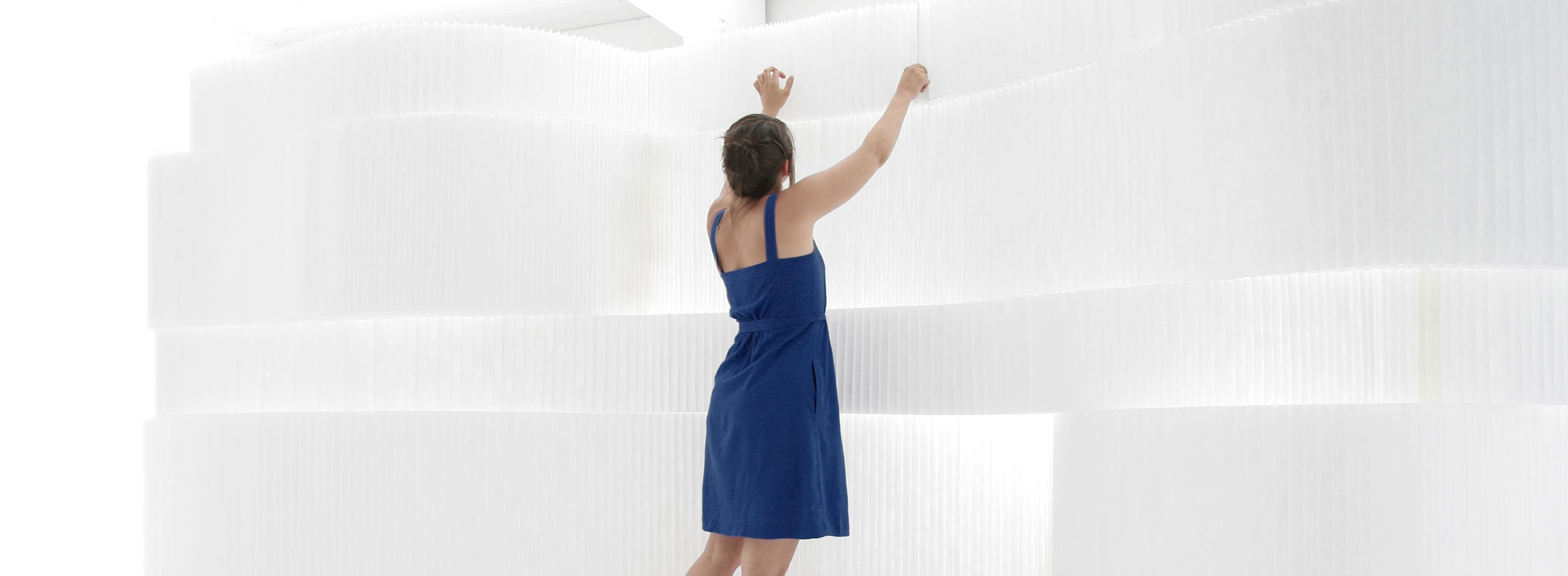 woman wearing a blue dress adjusts stacked white textile softblocks