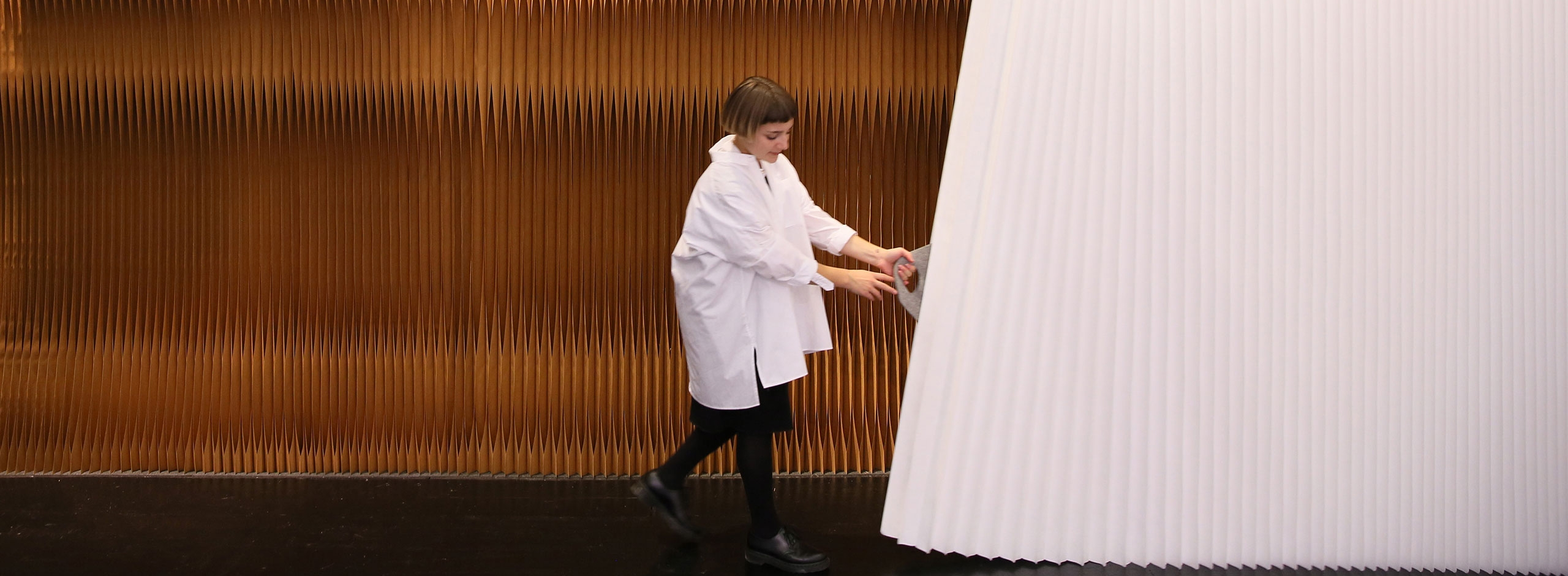 woman stretches open a white textile softwall