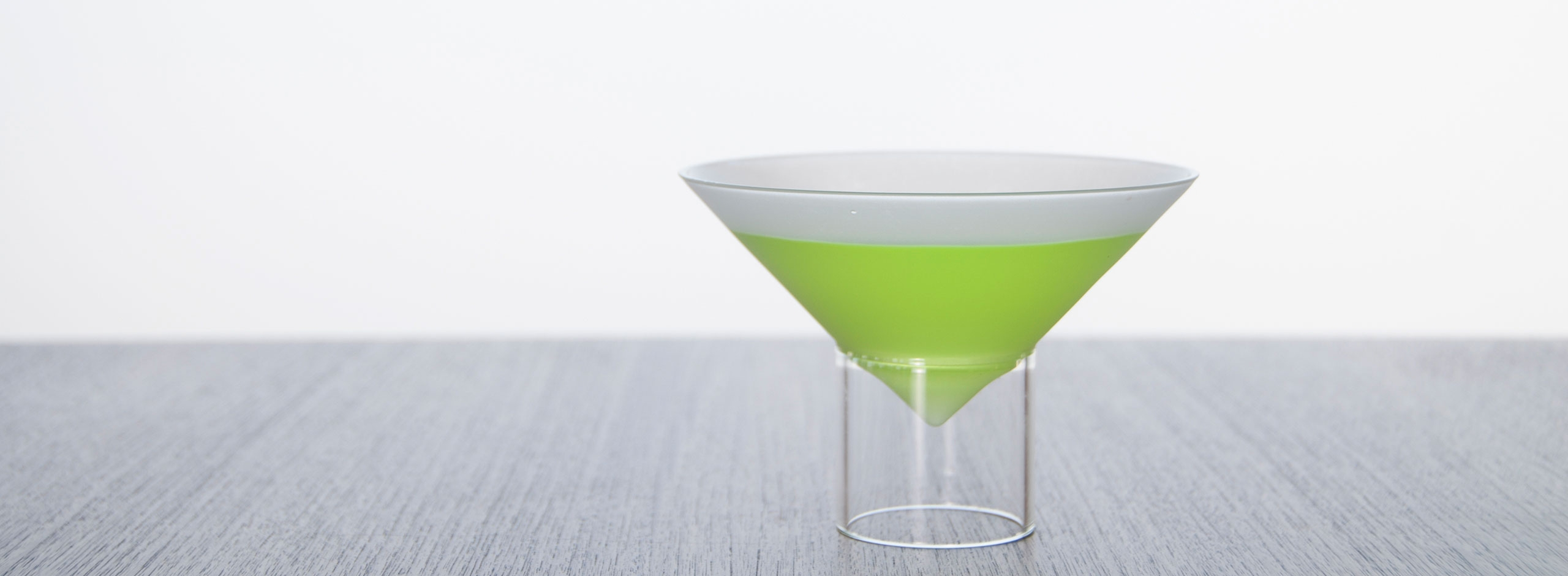 a bright green appletini in a float martini glass