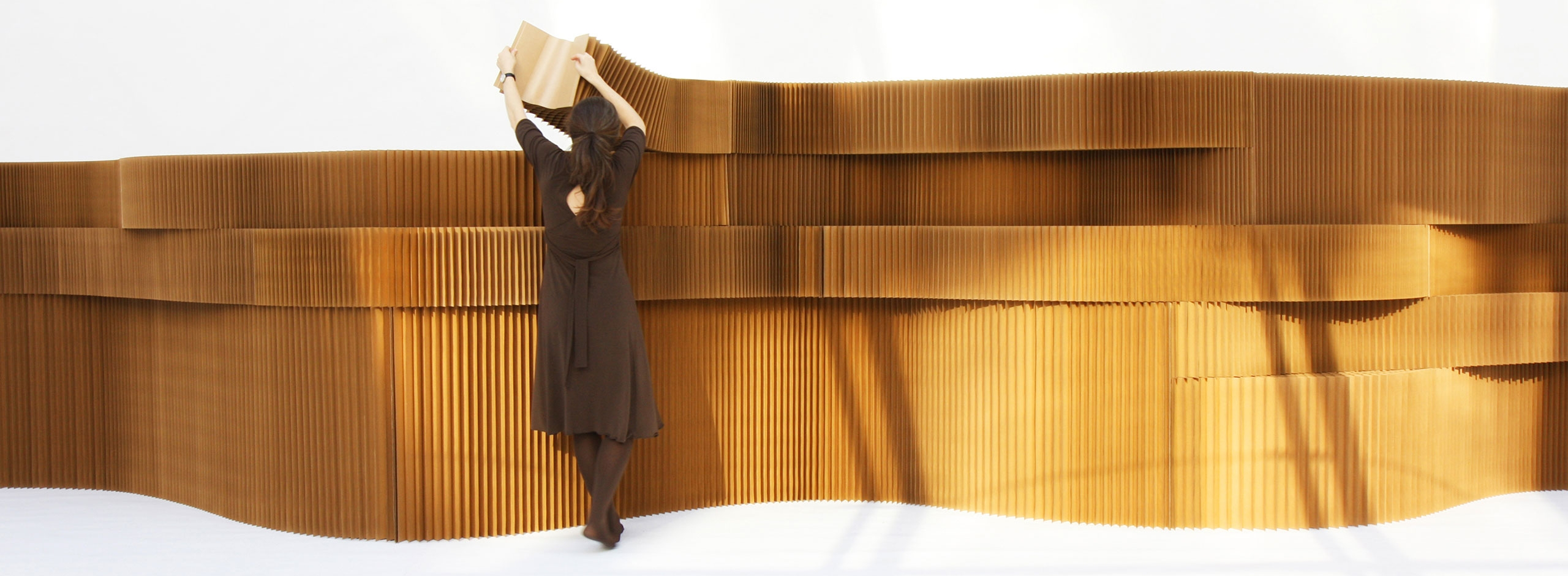 a woman arranges a series of stacked brown paper softblocks