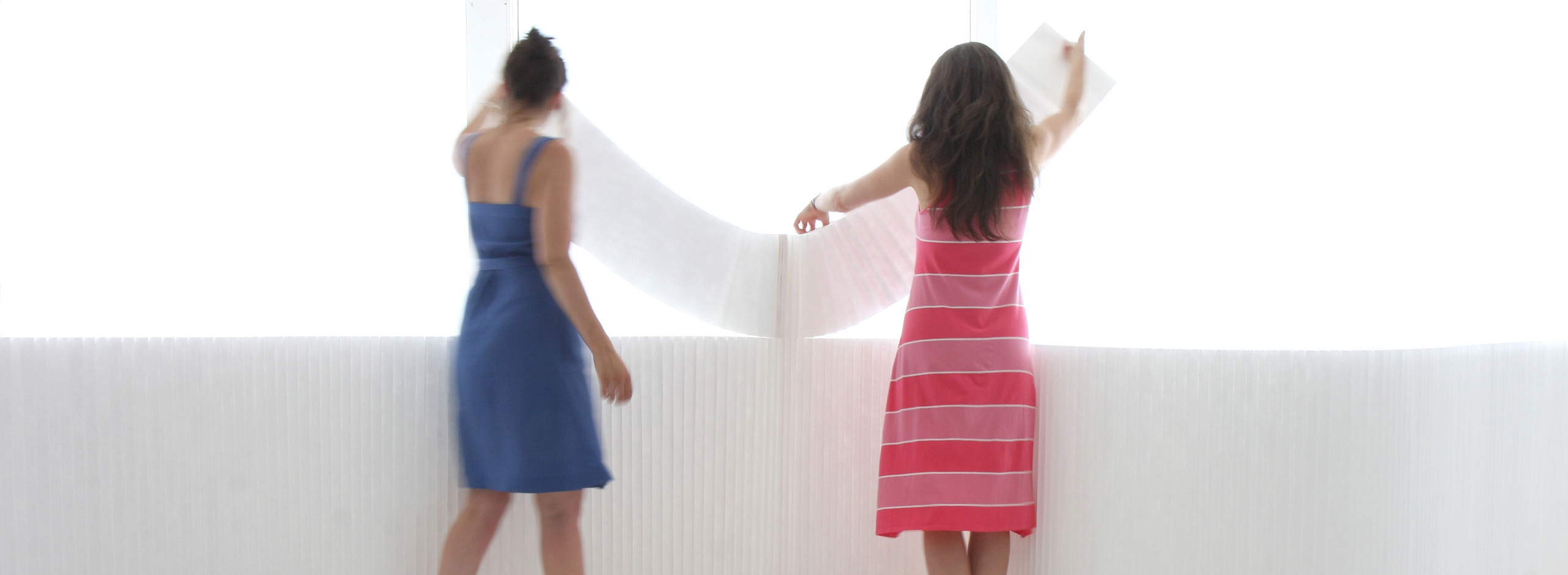 two women arrange white textile softblocks