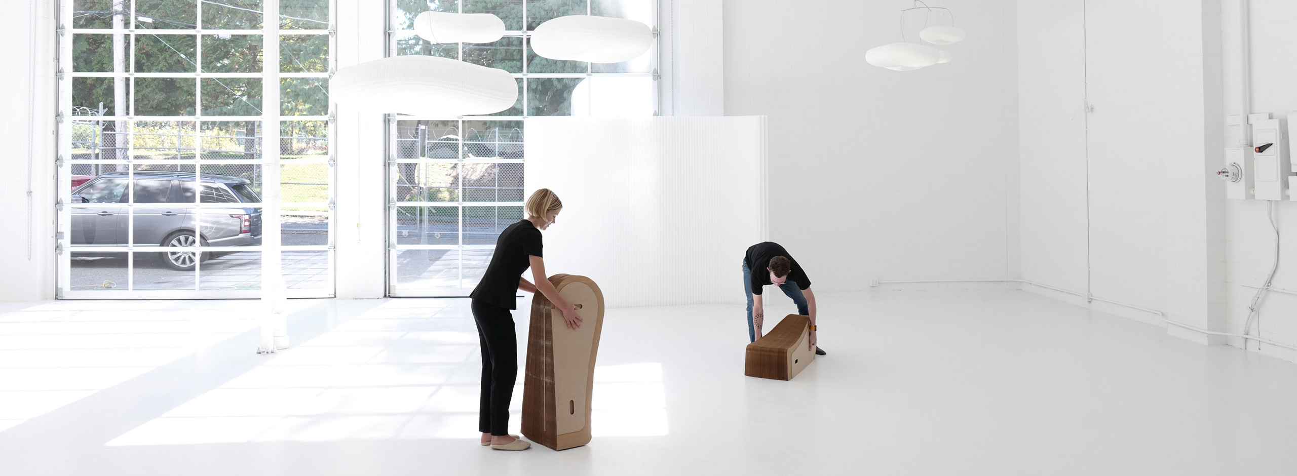 Folding paper furniture, two people compress a softseating lounger for storage.