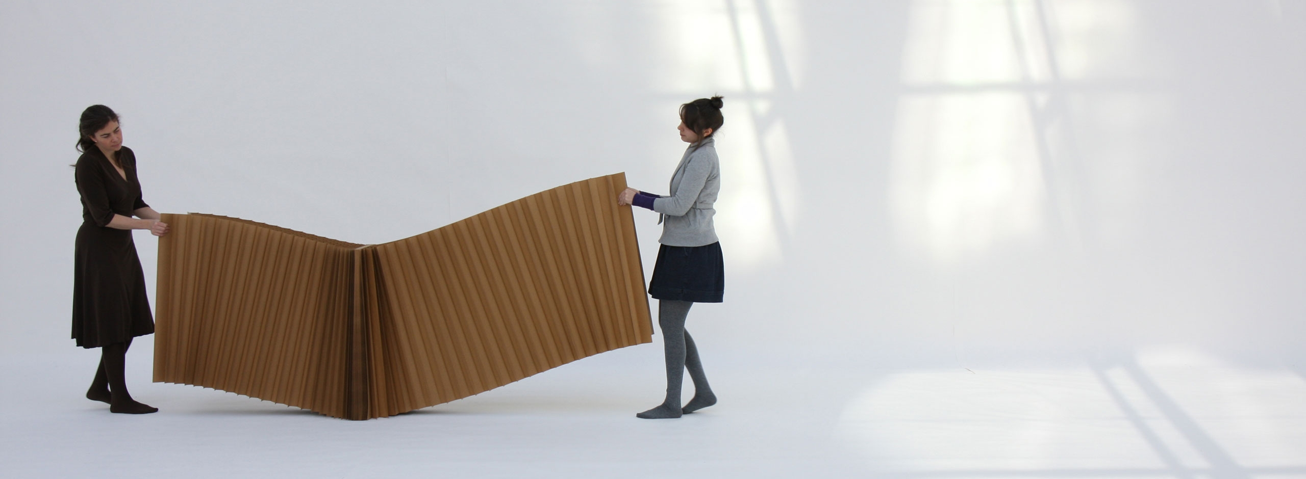 two women stretch open a brown paper softblock