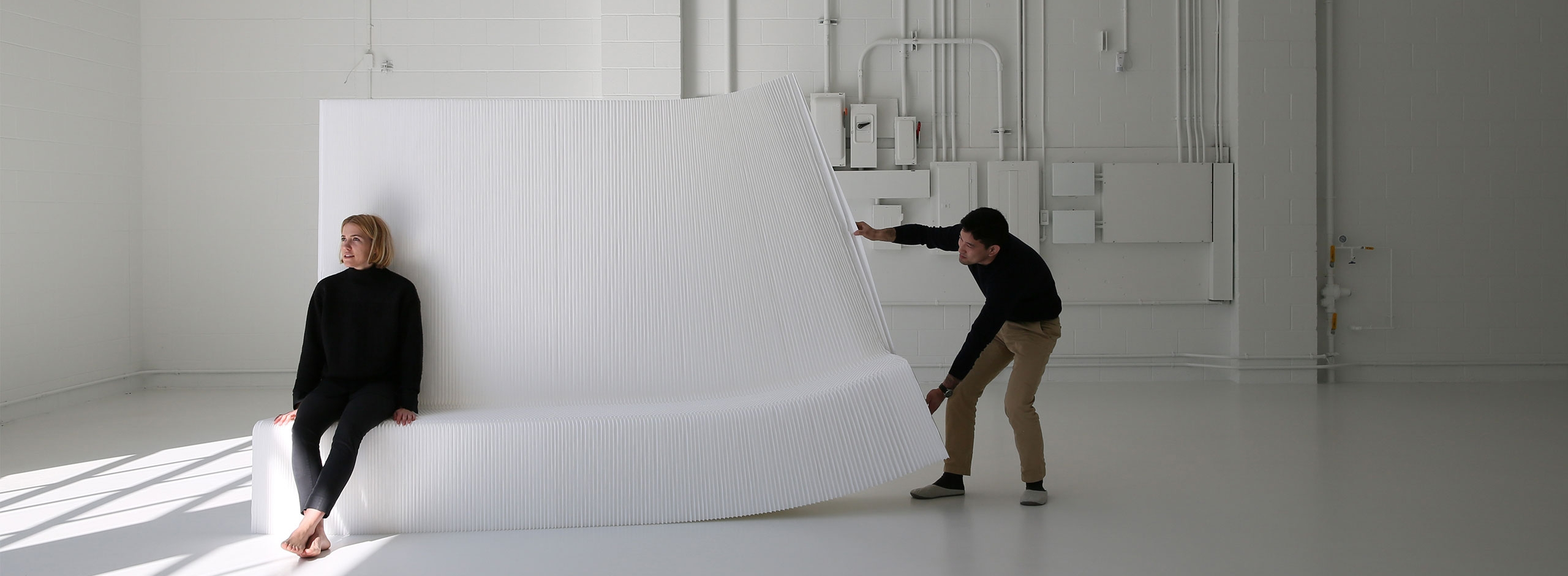a man tries to stretch open a white textile benchwall while a woman sits on it and weighs it down