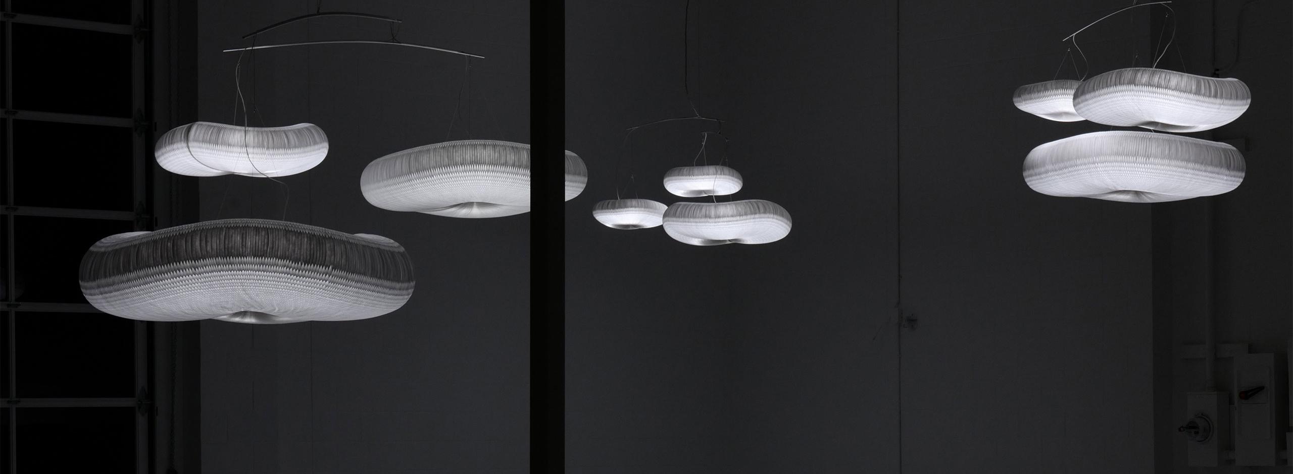 three cloud mobiles hang in the dark