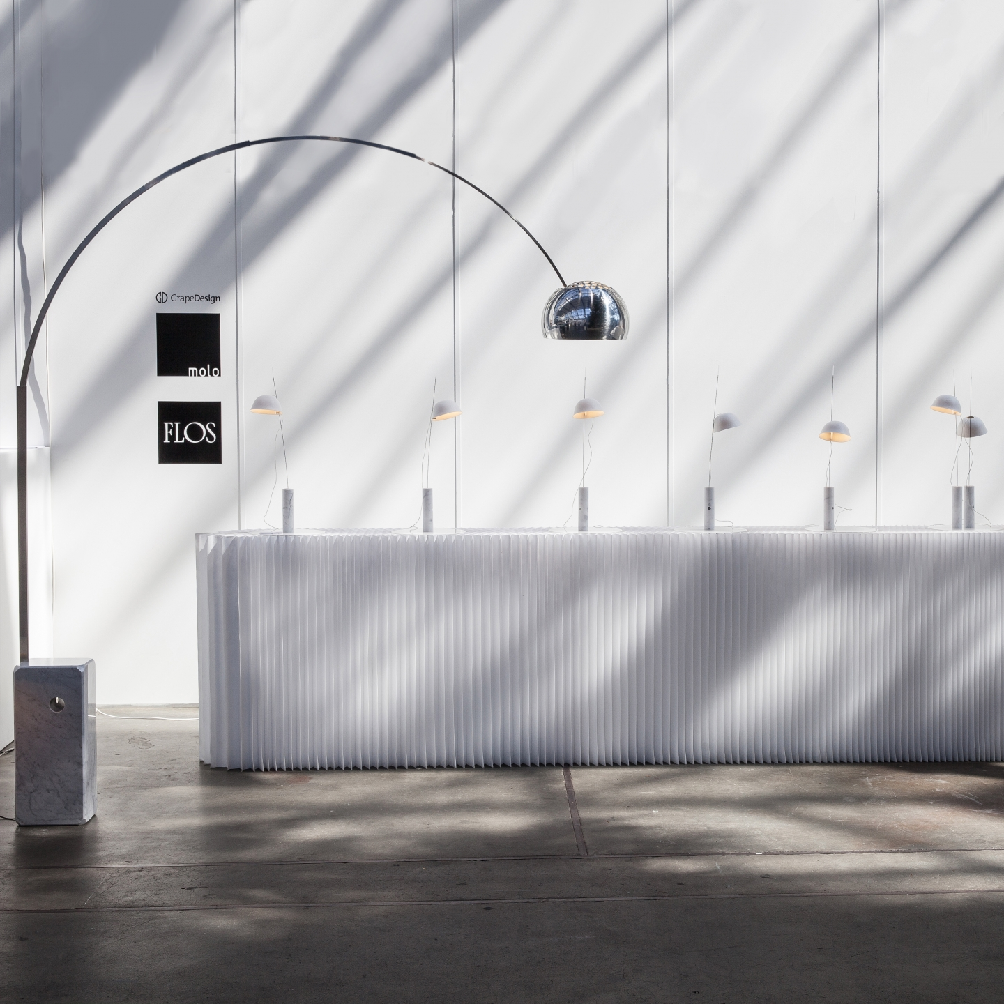 cappello light / table lamp by molo - the long curve of an Arco lamp frames a row of cappello