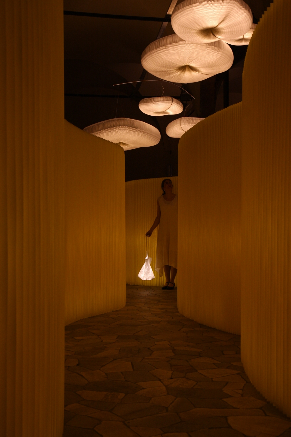 at night: textile softwall in a custom yellow colour and cloud softlight mobile for MOST in Milan - modern paper lighting
