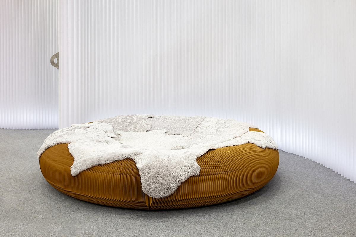 a kraft paper lounger covered with a sheepskin blanket