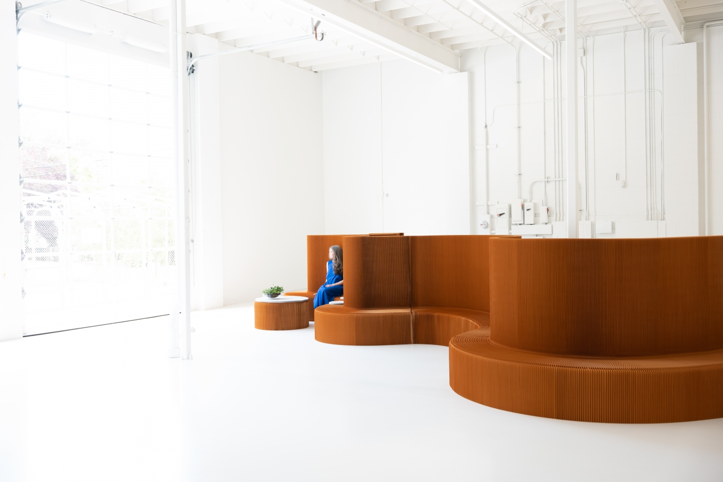 a woman sits at benchwall, a modular seat and partition system