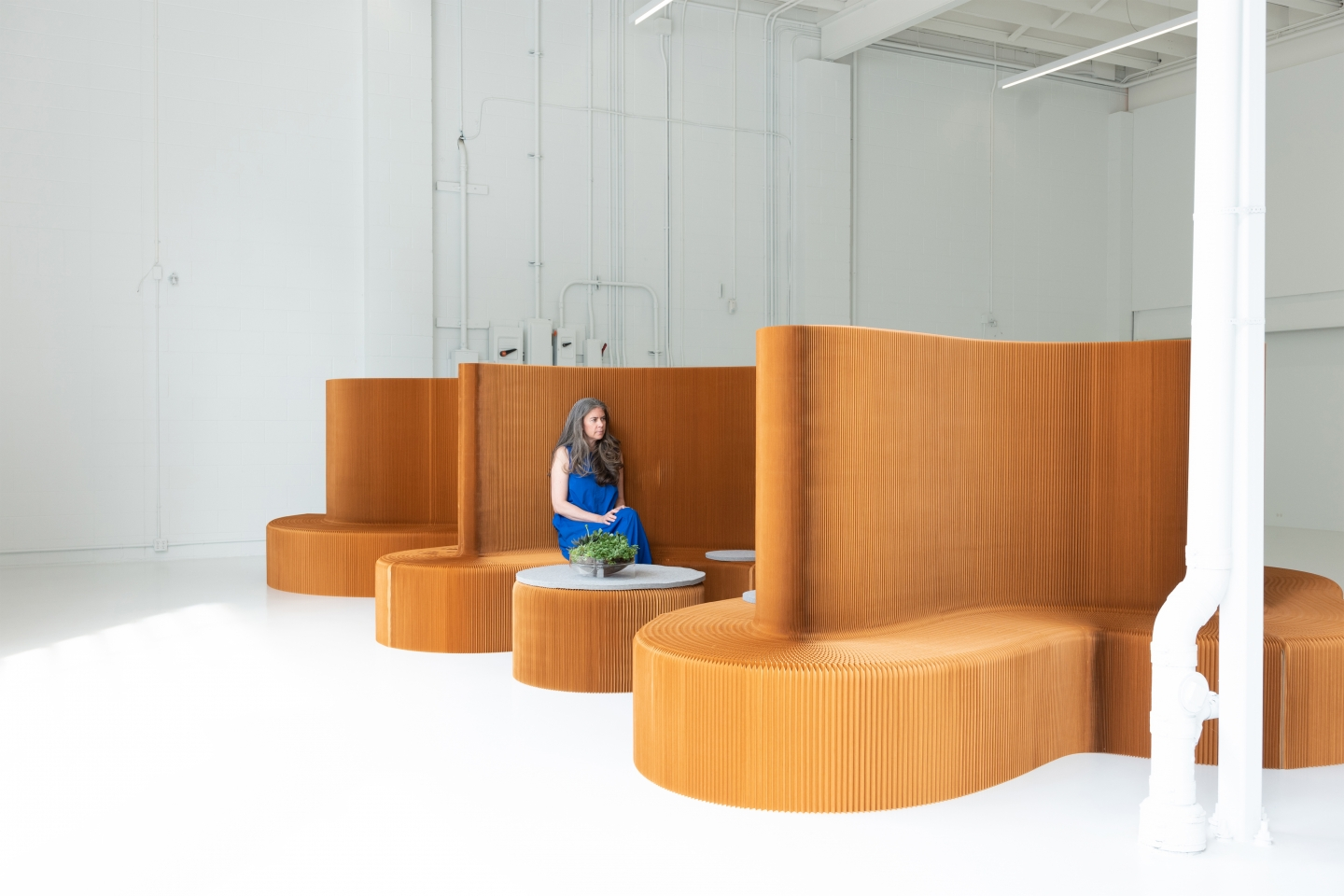 a woman sits in a meeting room made of benchwall, a foldable seat and room divider