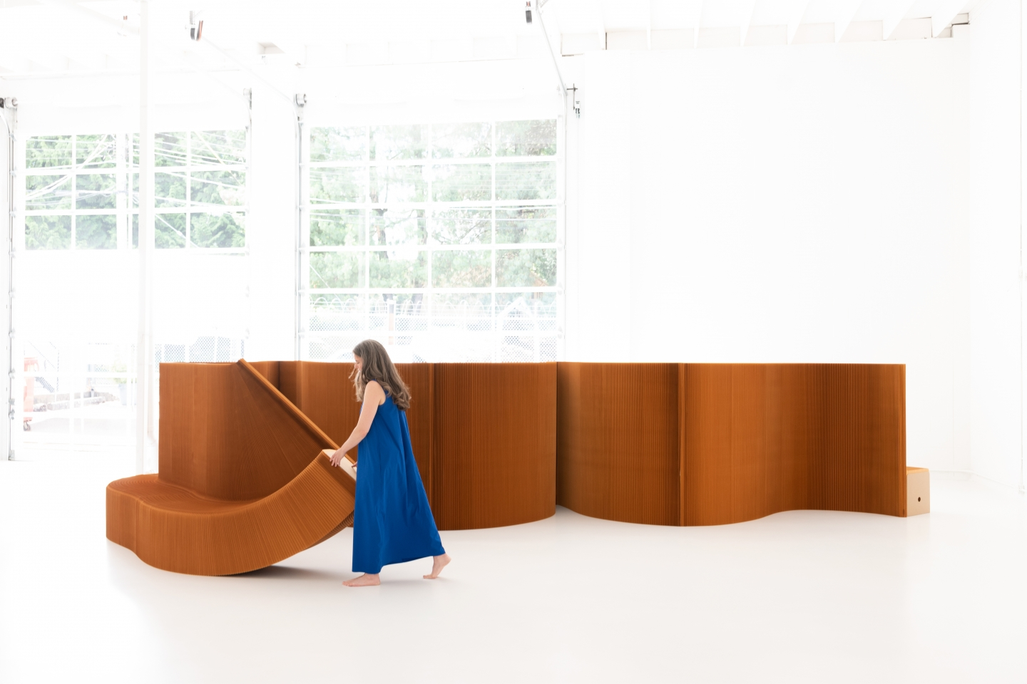 a woman rearranges benchwall, a flexible, moveable room divider and bench system