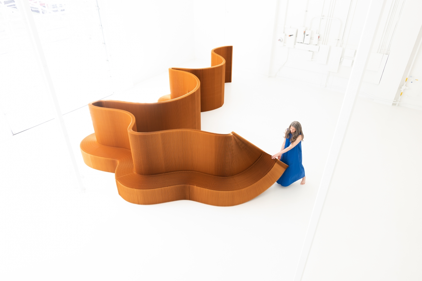 a woman rearranges paper benchwall, a flexible, foldable furniture system