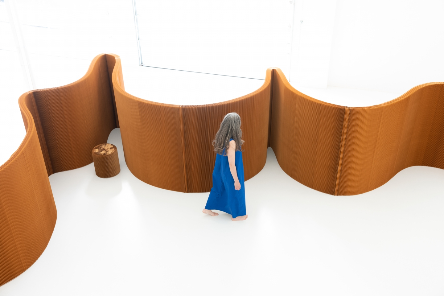 a woman explores paper furniture made into meeting room