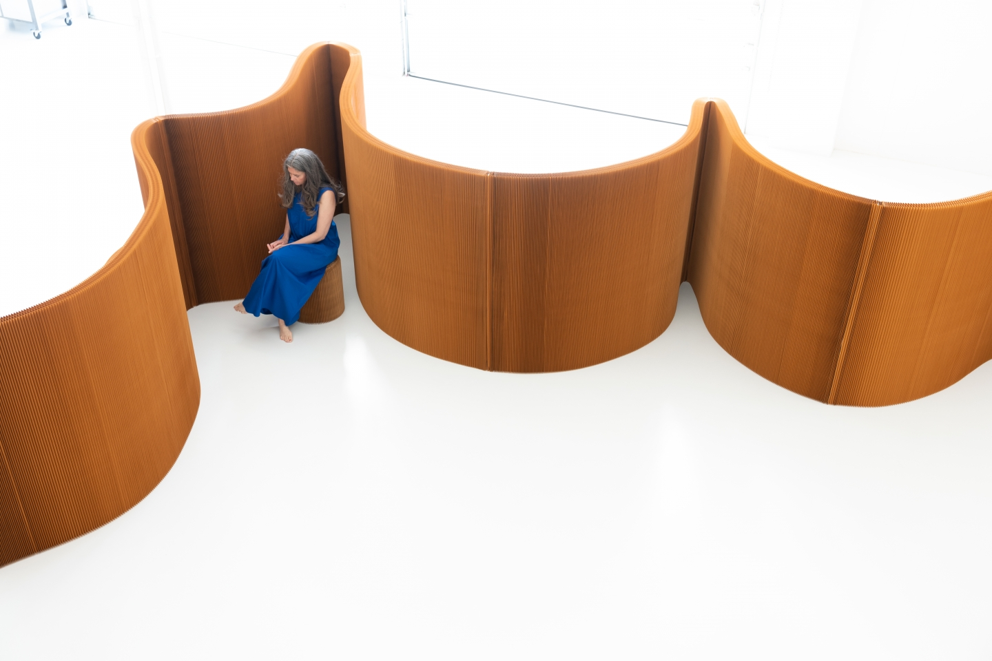 a woman sits on a folding paper stool behind benchwall, a paper furniture system