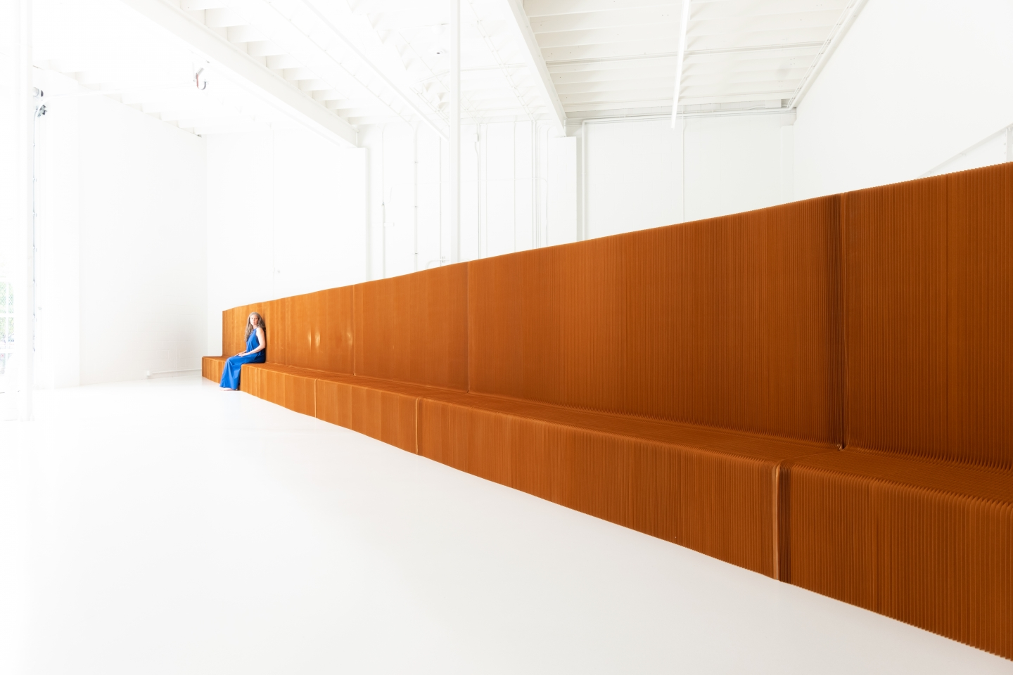 a woman sits on benchwall, an extendable, flexible bench and room divider