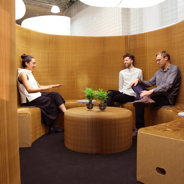 coworkers chat in a meeting room made from benchwall at ICFF