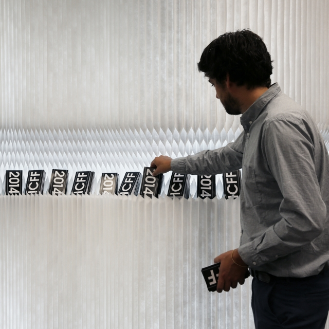 a man retrieves a postcard from a display cut into a softwall